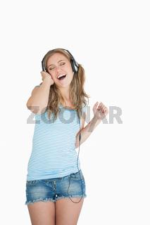 Young woman enjoying music over headphones
