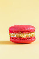 red Cake macaron or macaroon on yellow background.