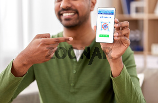 man with certificate of vaccination on smartphone