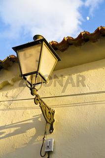 Street light on stone wall, spain.
