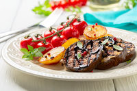 Grilled eggplant steaks with vegetables.