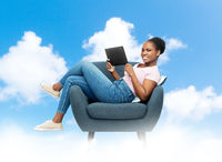 smiling woman with tablet pc sitting in armchair