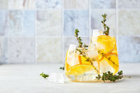 Refreshing cocktail with ice, orange and thyme. Refreshing summer homemade alcoholic or non-alcoholic cocktail or mocktail, or Detox infused flavored water