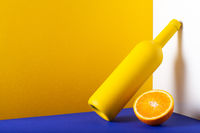 Yellow bottle and orange on the blue table.