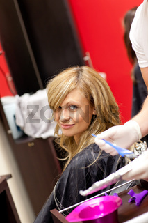 Smiling blond woman drying her hair