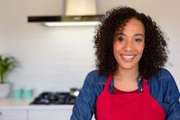 Portrait of happy african american woman wearing apron in kitchen