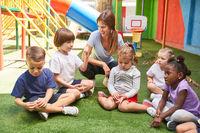 Kindergärtnerin redet mit Kindern in Kindertagesstätte