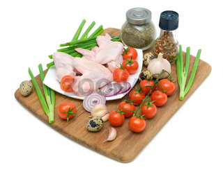 raw chicken wings, vegetables and eggs on a white background