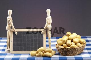 Korb mit Kartoffeln, Gliederpuppen und Schiefertafel auf karierter Tischdecke