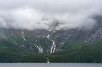 Several waterfalls drop down through lush green forest into a Norwegian fjord on the Helgeland Coast
