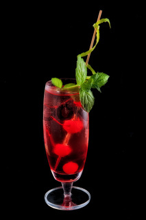 Alcohol red drink, cocktail with mint, cherry, isolated black