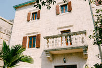Beautiful antique balcony in a light stone building with wooden shutters.