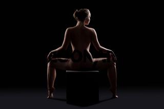 Beautiful nude woman posing on cube silhouette