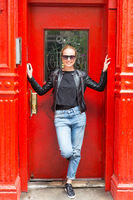 Fashionable Young Woman Wearing Sunglasses, Black Leather Jacket and Bleu Jeans Posing in front of Red Door on Street of New York City.