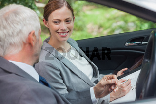 Smiling partners working together in classy car