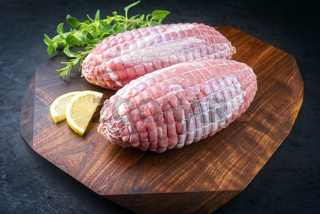 Modern style traditional raw veal roll roast with herbs and lemon slice offered as close-up on a design wooden board