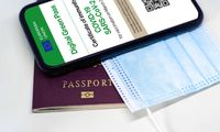 The digital green pass of the european union with the QR code on the screen of a mobile phone over a surgical mask and a passport