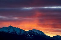 Rocky alpine mountain range during sunset with red illuminated clouds in Tirol, Austria
