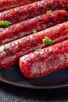 Grilled sausages close-up on a plate on a dark background. Frankfurter Bratwurst