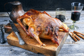 Traditional roasted stuffed Christmas goose with orange slices served as close-up on an old rustic wooden board