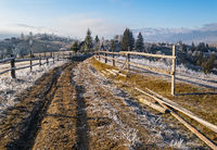 Winter coming. Last days of autumn, morning in mountain countryside peaceful picturesque hoarfrosted scene. Dirty road from hills to the village. Ukraine, Carpathian mountains.