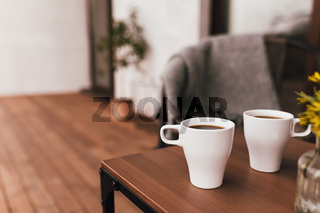 Two cups of coffee on the table on wooden brown terrace during evening sunset
