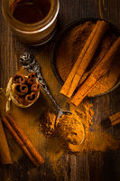 Assortment of cinnamon and gingerbread seasoning for cooking and baking on brown wooden background