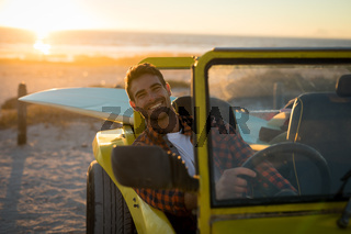Happy caucasian man sitting in beach buggy by the sea during sunset smiling