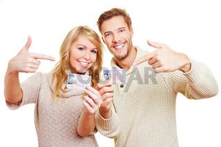 Zwei Jugendliche zeigen auf ihre Führerscheine