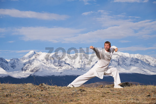 Wushu master in a white sports uniform training kungfu in nature on background of snowy mountains.