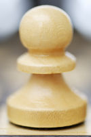 One Chess Pawn on white background with faint reflextion.