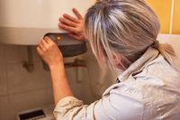 Frau als Hausfrau justiert den Durchlauferhitzer