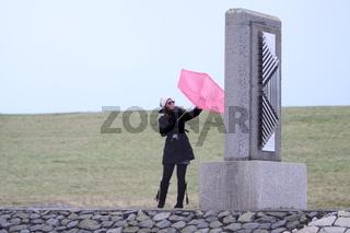 Junge Frau kämpft mit ihrem rosa Schirm gegen den Wind, Niederlande, Zeeland, Breskens