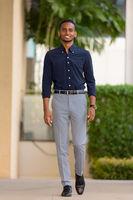 Full length shot of handsome African businessman outdoors walking