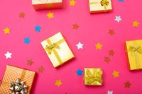 Composition of christmas decorations with presents and stars on pink background