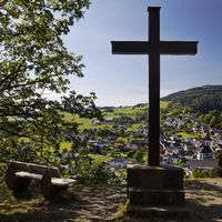 Cross of the Kreuzberg chapel with a view of the district Duedinghausen, Medebach, Germany