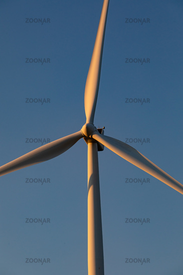 Close up of wind turbine in countryside landscape with cloudless sky
