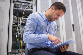 Man using tablet pc beside servers