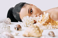 Fashion portrait of beautiful african american woman with different seashells looking through conch
