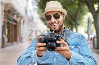Handsome tourist checking photos in digital camera.