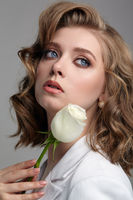 Woman in white jacket with blue eyes and white rose flower in hands near face.