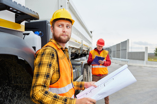 Arbeiter mit Bauzeichnung vor einem LKW
