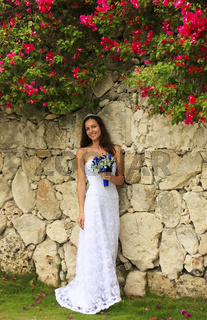 Young woman in wedding dress posing in front of the stone wall with flowers