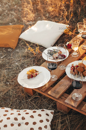 Wooden table with glassware arranged for picnic