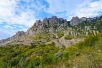 Autumn mountain landscape - yellow and green trees against the background of rocky stone mountains and blue sky with white clouds on a sunny day