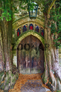 Wooden Door of St Edwards church with two ancient yew trees, Stow-on-the-wold, Cotswolds, UK