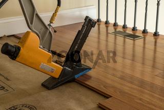 High pressure nail gun ready to install sections of Brazilian Cherry hardwood flooring