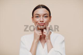 Young woman doing face building facial gymnastics self massage and rejuvenating exercises