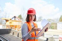 Architektin mit Prüfprotokoll auf der Baustelle