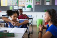 African american female teacher and a girl talking in hand sign language at elementary school